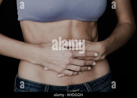 Woman clutching bare stomach with hands - Stock Image