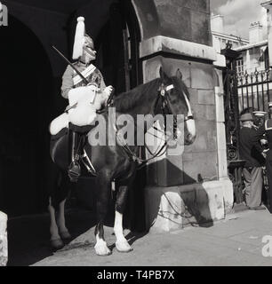 1960s, historical, London, Summer time and a Horseguard in full ceremonial uniform on his horse doing on sentry duty, - Stock Image