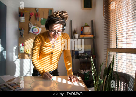 Woman painting and listening to music - Stock Image