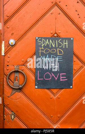 Sign pinned to the colourful door of a Spanish restaurant in the Old Town quarter of Tallinn, Estonia. - Stock Image