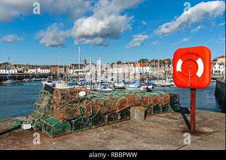 Anstruther harbour in Anstruther Fife Scotland with boats moored and with fishing gear & life belt on pier - Stock Image