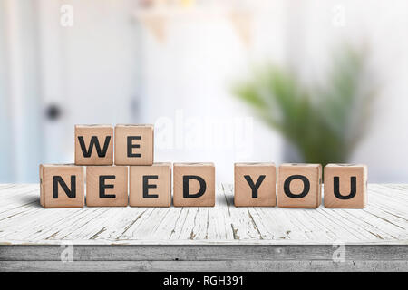 We need you sign on a white table in a bright room with a green plant - Stock Image