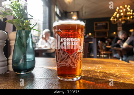 A pint of Fuller's London Pride beer on a wooden tabletop in a pub - Stock Image
