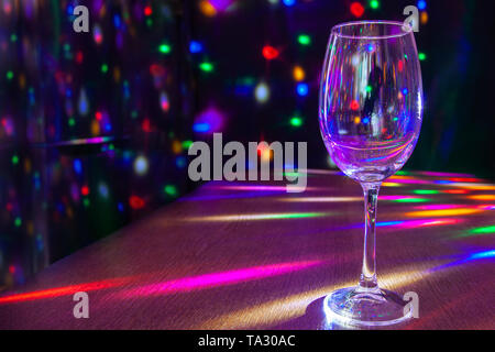 glass on the table in the restaurant with bright festive lighting closeup - Stock Image