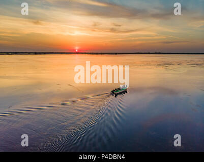 Tourists visiting Danube Delta at sunset in a motor boat. Sunset in Danube Delta (Delta Dunarii), Europe, Romania - Stock Image