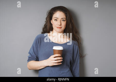 relaxed young woman on her coffee break - holding coffee to go in disposable paper cup while leaning against gray wall - Stock Image