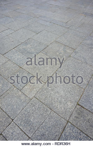Pavement made of gray old tiles in soft focus - Stock Image