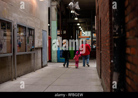 A family walks down and alley in Ithaca NY, SA - Stock Image