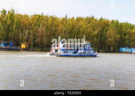 The Danube Delta Biosphere Reserve, Romania. April 20, 2019. A small cruise ship travels along the river. - Stock Image