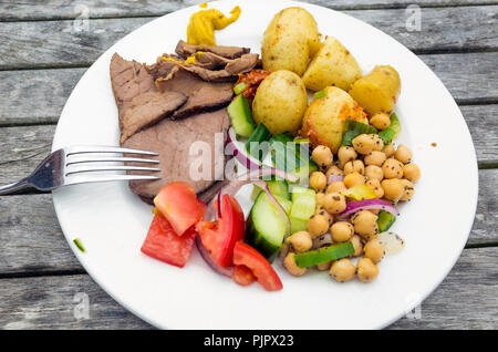 Lunch outdoors cold roast beef with salad chick peas and roasted new potatoes - Stock Image