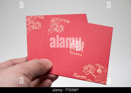 hand holding chinese red pocket for weddings - Stock Image