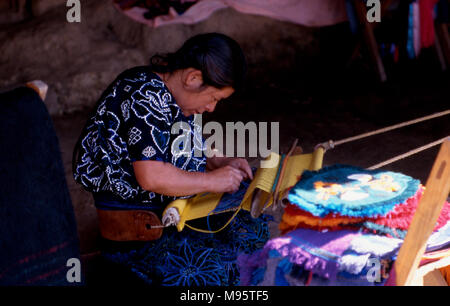 An indigenous Tzotzil Maya woman makes clothes the traditional Mayan way, weaving on a back-strap loom. Chiapas State, Mexico. - Stock Image