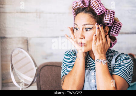 Beautiful and funny expression caucasian adult woman getting ready at home in front of the mirror with make up on the face - wrinkles checking and get - Stock Image