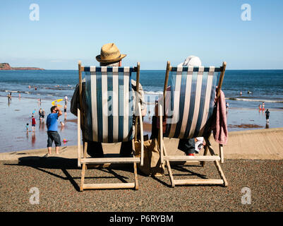 Hatted Couple enjoying the English Summer heatwave by the seaside in traditional striped Deck chairs with views of beach in Dawlish, England, Europe. - Stock Image