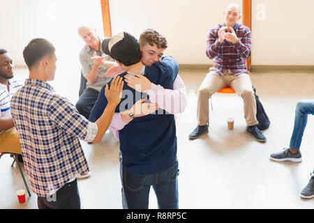Men hugging and clapping in group therapy - Stock Image