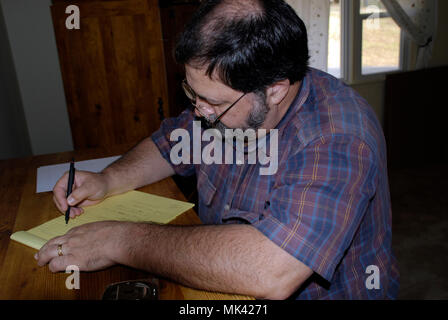 man doing some  research on legal pad (model released) - Stock Image