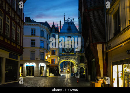 colorful evening sky over the Normandy medieval city of Rouen France as locals and tourists pass under the Gros Horloge, or astronomical clock. - Stock Image