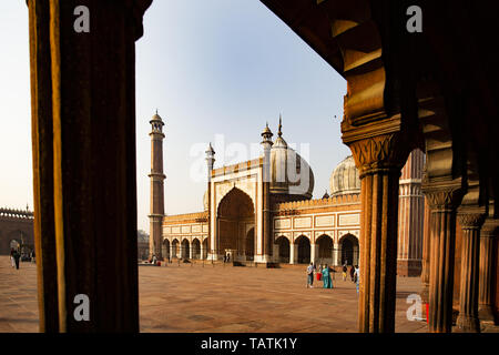 Some tourists are taking photos in front of the beautiful Jama Masjid in New Delhi during sunset. Jama Masjid is one of the largest mosques in India. - Stock Image