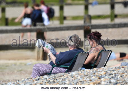 Littlehampton, UK. Wednesday 27th June 2018. People on the beach reading a newspaper on another very warm and sunny morning in Littlehampton, on the South Coast. Credit: Geoff Smith / Alamy Live News. - Stock Image