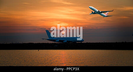 Sydney, New South Wales, Australia - August 1. 2014: Virgin Airlines commercial passenger jet departing Sir Kingsford Smith Airport Mascott, at sunset - Stock Image