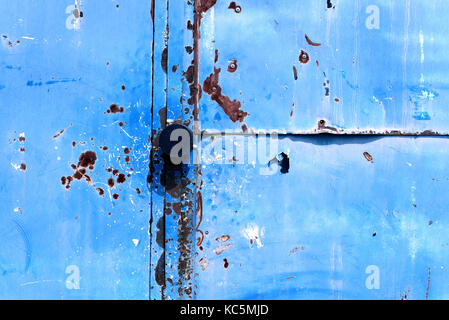 Old retro vintage door handle with a blue flaking paint metal background - Stock Image