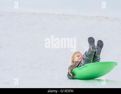 Boy playing on toboggan in snow - Stock Image