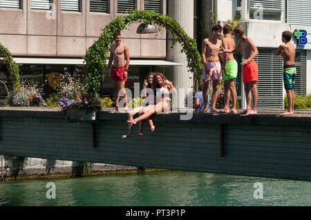 Young residents preparing to dive into the glacial waters of the river Aare on a hot summer day, at Thun, Switzerland - Stock Image