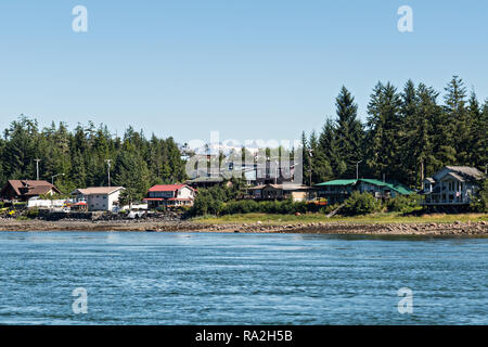 The tiny hamlet of Kupreanof across the Wrangell Narrows from Petersburg with the Alaska Coast Range of mountains behind in southeast Alaska. - Stock Image