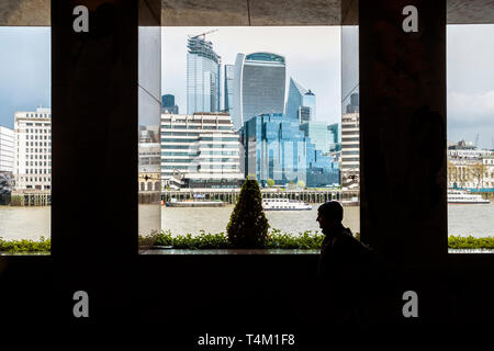 Iconic high rise buildings seen between pillars of a building on the South Bank in London. - Stock Image