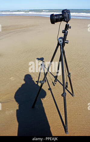 A camera on tripod with shadows including photographer on a sandy beach in North Norfolk, England, United Kingdom, Europe. - Stock Image
