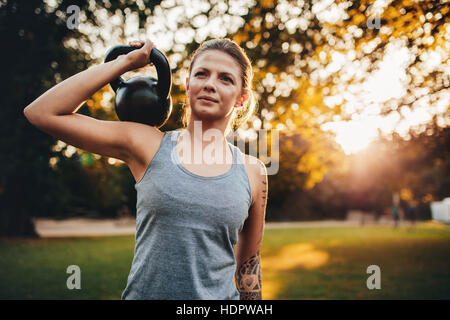 Portrait of fit young woman with kettlebell weights in the park. Fitness woman training with weights in park. - Stock Image