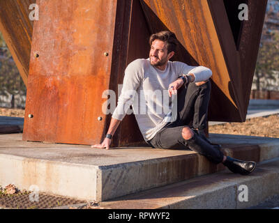 One handsome man in city setting sitting by rusty metal structure - Stock Image