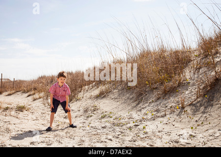 child playing soccer at beach - Stock Image