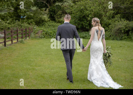 couple walk away from the camera at their Wedding, Jennycliff, Plymouth, Devon, UK - Stock Image