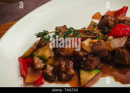Meat stew with zucchini, sweet pepper and thyme. Cafe menu on a wooden background in warm colors with copy space. - Stock Image