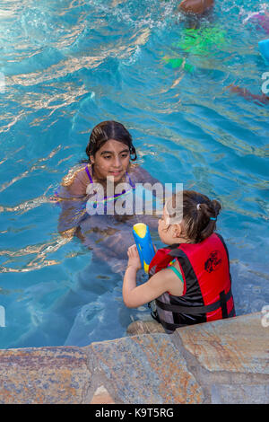 girls, children, playing, squirting water soaker, swimming pool, freshwater swimming pool, pool party, Castro Valley, - Stock Image