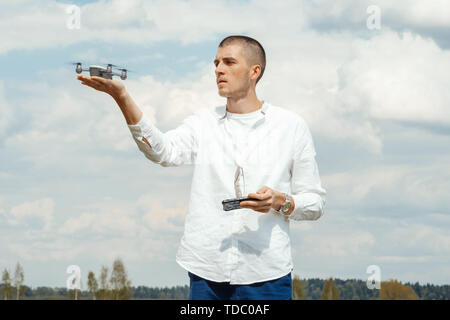 Young handsome man with drone quadcopter on his hand at countryside at sunny day. - Stock Image