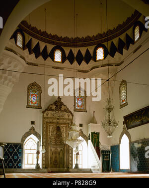 Turkey. Asia Minor. Bursa. Muradiye Complex. View of the inside of Muradiye Mosque. Its construction was ordered by the sultan Murat II (Reigned 1421-1451), it was completed in 1426. Walls decorated with hexagonal tiles in turquoise and dark blue. Mihrab carved in stone and Minbar (pulpit). - Stock Image