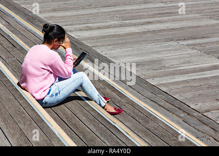 A young Asian woman online using her mobile phone in Victoria Harbour in Melbourne Docklands,Victoria Australia. - Stock Image