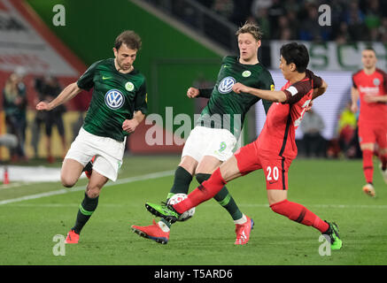 Wolfsburg, Germany. 22nd Apr, 2019. Soccer: Bundesliga, 30th matchday: VfL Wolfsburg - Eintracht Frankfurt in the Volkswagen Arena. Wolfsburg's Admir Mehmedi (l) and Wout Weghorst and Frankfurt's Makoto Hasebe (r) fight for the ball. Credit: Peter Steffen/dpa - IMPORTANT NOTE: In accordance with the requirements of the DFL Deutsche Fußball Liga or the DFB Deutscher Fußball-Bund, it is prohibited to use or have used photographs taken in the stadium and/or the match in the form of sequence images and/or video-like photo sequences./dpa/Alamy Live News - Stock Image