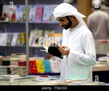 Abu Dhabi, United Arab Emirates (UAE). 24th Apr, 2019. A man reads a book displayed at the 29th edition of Abu Dhabi International Book Fair, in Abu Dhabi, the United Arab Emirates (UAE), April 24, 2019. The 29th edition of Abu Dhabi International Book Fair kicked off on Wednesday at the Abu Dhabi National Exhibition Centre, with more than 500,000 titles on display. Credit: Su Xiaopo/Xinhua/Alamy Live News - Stock Image