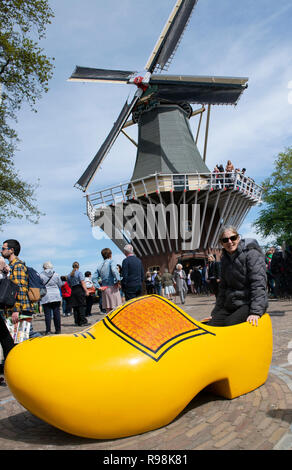 Female tourist sits in copy of yellow clog in front of a windmill in the  Keukenhof Park the world's largest bulb garden  Lisse, Holland, Netherlands - Stock Image