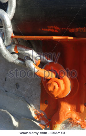 Steel chain painted with red oxide anti rust paint bolted to concrete - Stock Image