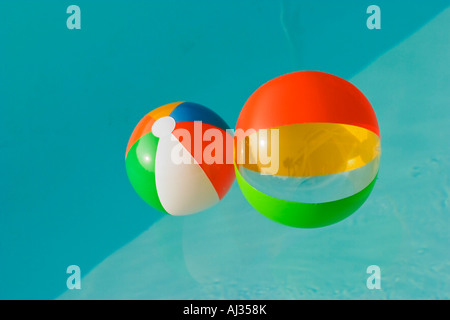 Two colorful beach balls floating in a swimming pool full of blue water - Stock Image