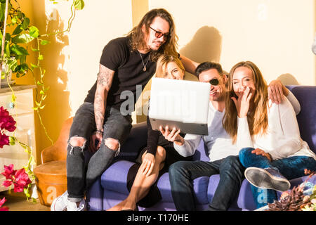 Group of friends have fun with laptop sitting on a sofa all together in friendship - caucasian hipster young people laugh and smile using technology a - Stock Image