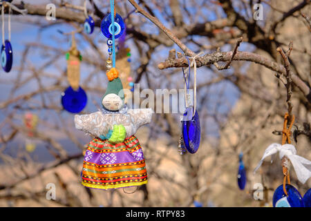 Public tree decorated with Evil Eye and doll pendants and other ornaments on a Cappadocia road side.  Blurry background of local rock formation - Stock Image