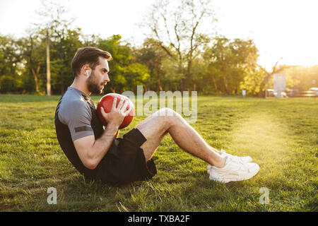 Image of a handsome young strong sports man posing outdoors at the nature park location make exercises with ball. - Stock Image