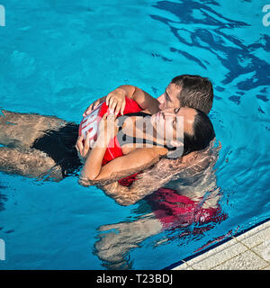 Lifeguard rescuing woman from swimming pool. - Stock Image