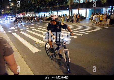Policeman on bicycle bike patrol, Waikiki, Honolulu, Hawaii - Stock Image