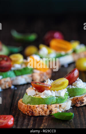 Avocado toast sandwich with avocadeos, fresh from the garden heirloom tomatoes and feta cheese, Greek food and healthy vegetarian diet concept, over a - Stock Image